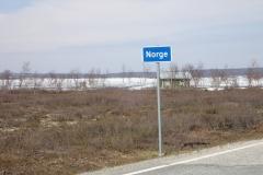 das offizielle Schild von Norwegen und dahinter der See voller Eis