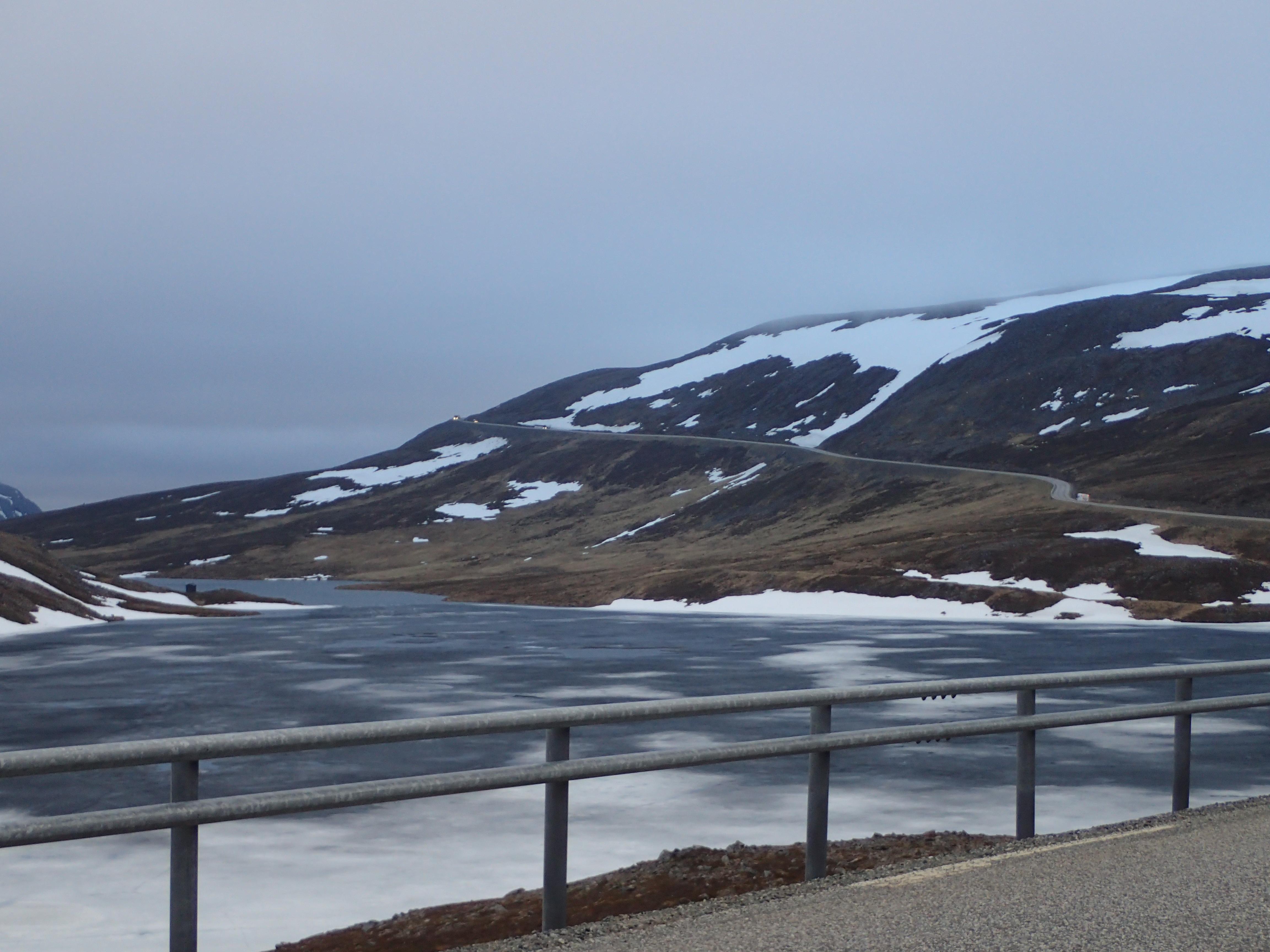 Bergsee und die Straße schlängelt sich am Berghang hoch